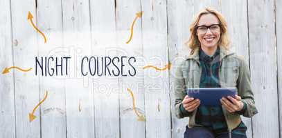 Night courses against smiling blonde in glasses using tablet pc