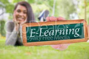 E-learning against pretty brunette smiling at camera in park