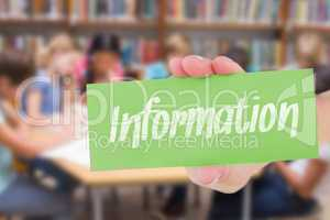 Information against cute pupils writing at desk in library