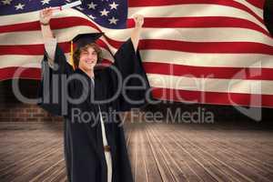 Composite image of male student in graduate robe raising his arm