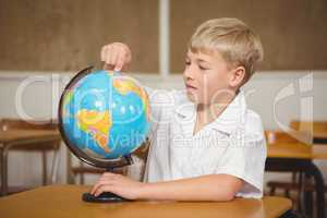 Pupil pointing to a place on a globe