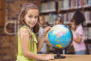 Pupil in library pointing to globe