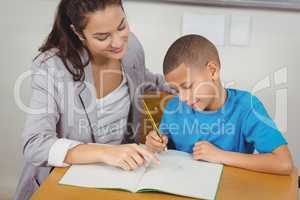 Pretty teacher helping pupil at his desk
