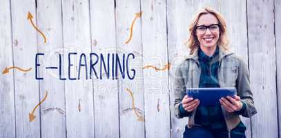 E-learning against smiling blonde in glasses using tablet pc