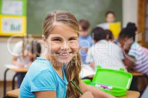 Pupil smiling at camera in classroom