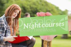 Night courses against pretty student studying outside on campus