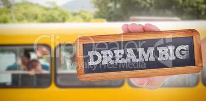 Dream big against cute pupils smiling at camera in the school bu