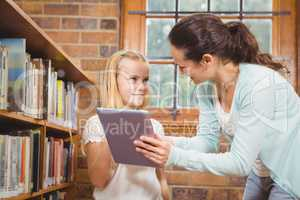 Teacher helping a student use a tablet