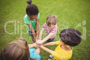Diverse classmates putting hands together