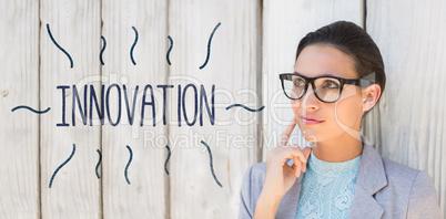 Innovation against stylish brunette thinking and smiling