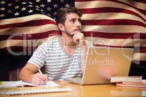 Composite image of student studying in the library with laptop