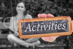 Activities against smiling student sitting on bench listening mu