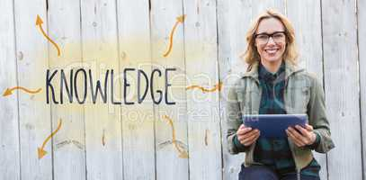 Knowledge against smiling blonde in glasses using tablet pc