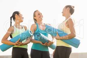 Laughing sporty women with exercise mats