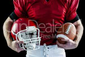American football player holding helmet