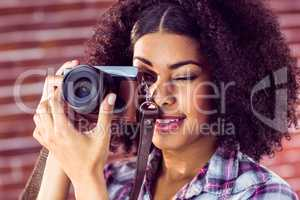 Attractive young woman photographing with camera