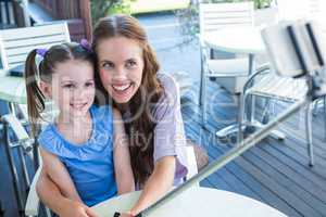 Mother and daughter using selfie stick at cafe terrace