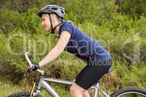 Smiling athletic blonde mountain biking