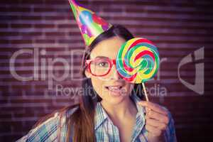 Pretty hipster with party hat and lollipop
