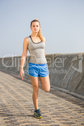 Sporty blonde stretching leg at promenade