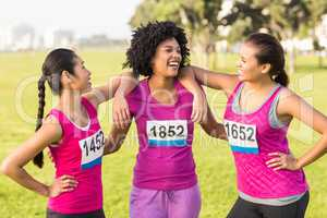 Three laughing runners supporting breast cancer marathon