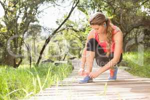 Blonde athlete tying shoelace on wooden trail