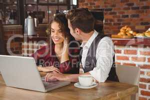 Cute couple on a date watching photos on a laptop
