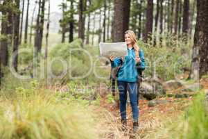Young pretty hiker using compass and map