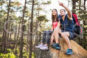 Young happy joggers sitting on rock feeling and pointing at some