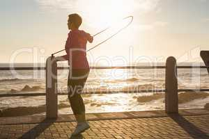 Sporty woman skipping at promenade