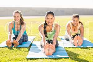 Smiling sporty women stretching on exercise mat