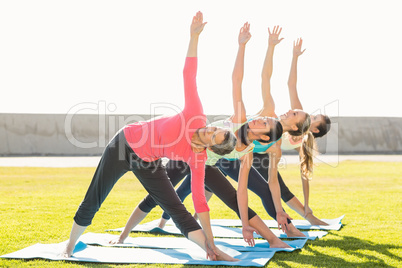 Sporty women doing triangle pose in yoga class