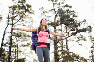 Young happy jogger standing on rock feeling free