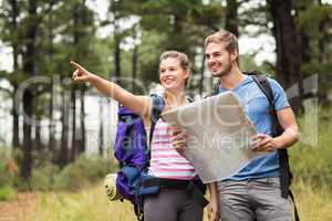 Young happy hikers pointing in the distance with a map