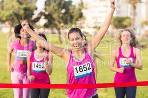 Cheering brunette winning breast cancer marathon