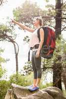 Smiling blonde hiker pointing far away