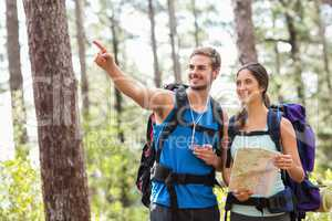 Happy hikers looking away holding map and compass