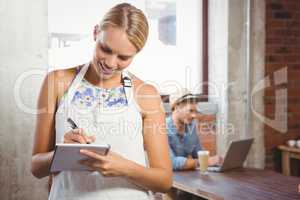 Smiling blonde waitress taking order in front of customer