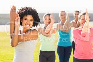 Smiling sporty women doing eagle pose in yoga class