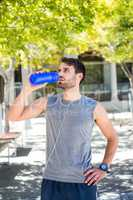 Handsome runner drinking water with hands on hips