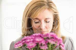 Casual businesswoman smelling at flowers
