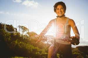 Smiling athletic brunette sitting on mountain bike