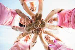 Women wearing pink for breast cancer and putting hands together