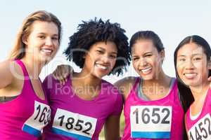 Four smiling runners supporting breast cancer marathon
