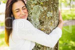 Beautiful brunette hugging a tree