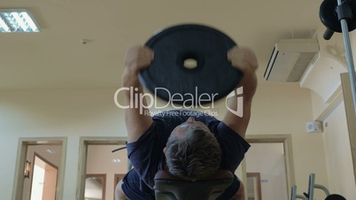 Exercise with lifting weight plate lying on bench