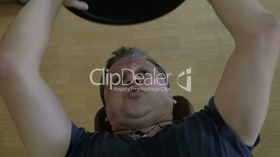 Man finishing exercise with weight plate