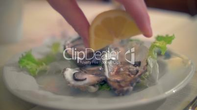 Pouring lemon juice on oysters