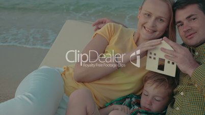 Family with house model as real estate concept