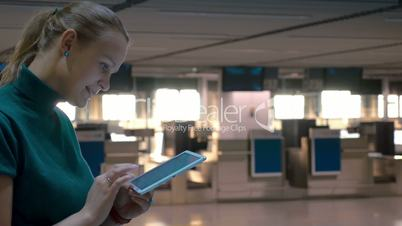 Woman with Tablet by Airport Check-In Counters